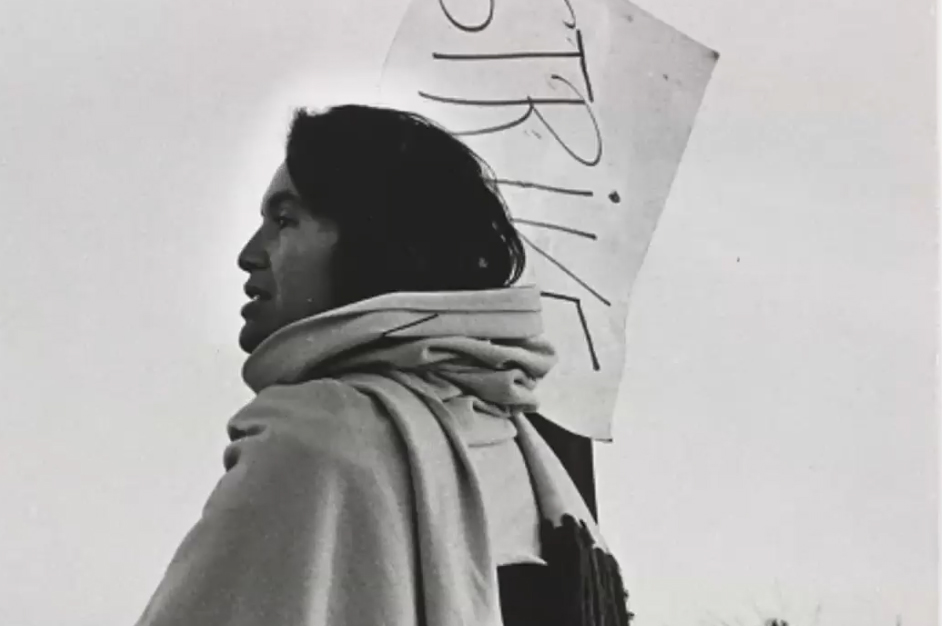 black and white photo of a woman holding a protest sign