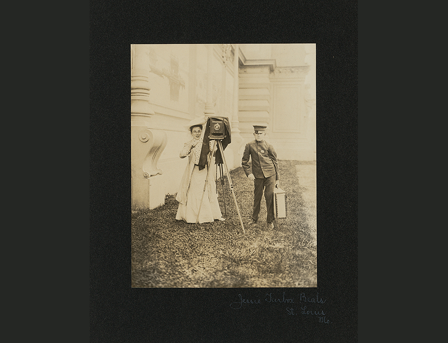 early 20th century image of a woman with a camera standing with a man