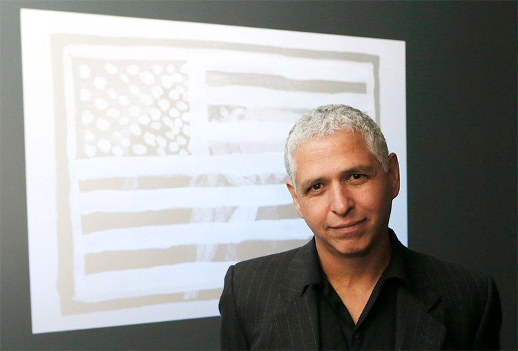 man with gray hair wearing a black shirt standing in front of a video