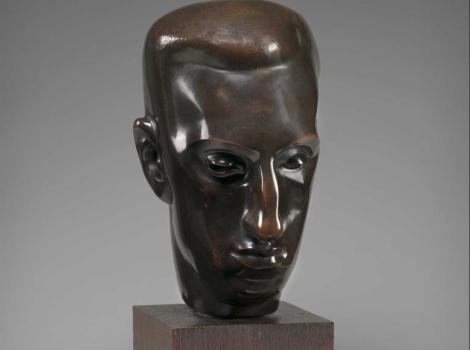 A photograph of a bust on a wooden pedestal
