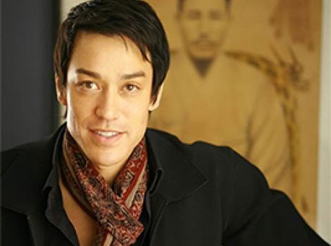 waist length photo of a young Asian man in a black sweater and patterned scarf