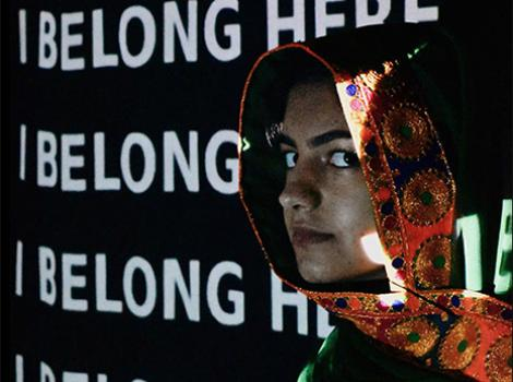 young Muslim woman in front of a projection of I Belong Here
