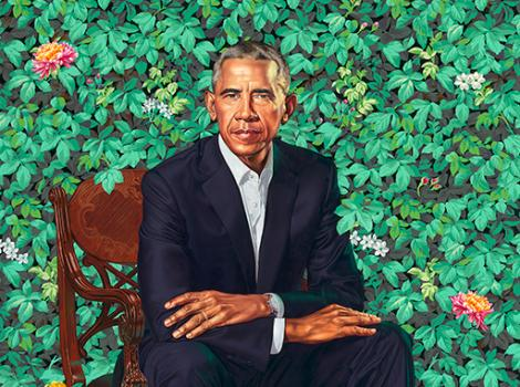 President Barack Obama seated against green foliage