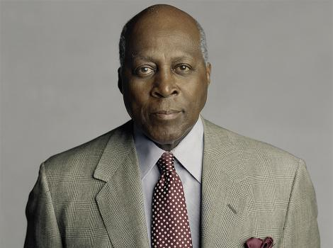 Older African American man in a patterned blazer and polka-dot tie