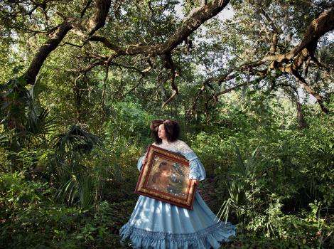 Woman in a long blue dress carrying a portrait through a wooded area