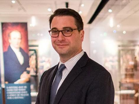 bust length photo of a man wearing glasses and wearing a suit in an exhibition space