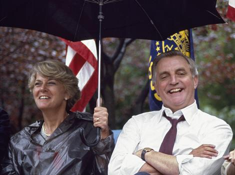 man and woman sitting in the rain and the woman holds an umbrella