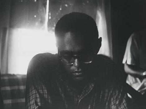 Black man in glasses seated before a window