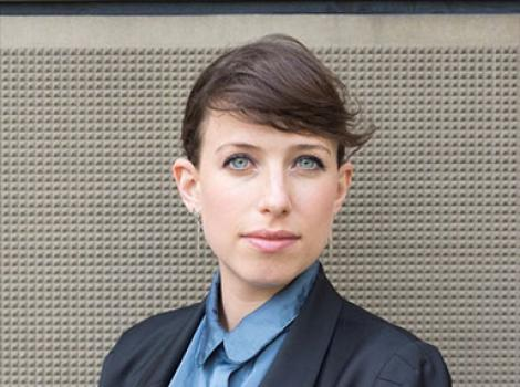 woman with dark hair and blue eyes wearing a blue blouse and blue blazer