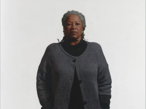 African American woman in a gray sweater against a white background