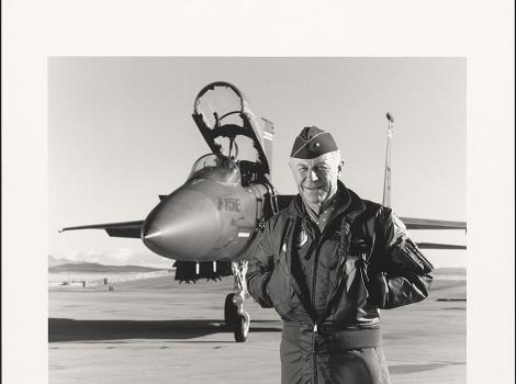 older man in a flight suit standing in front of a jet