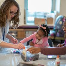 Child and two women working on a craft project