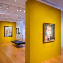 Exhibition space with yellow panels displaying portraits.