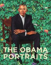 portrait of an African American man in a suit seated in a green leafy setting