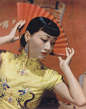 Asian American woman in a yellow dress with a fan behind her head