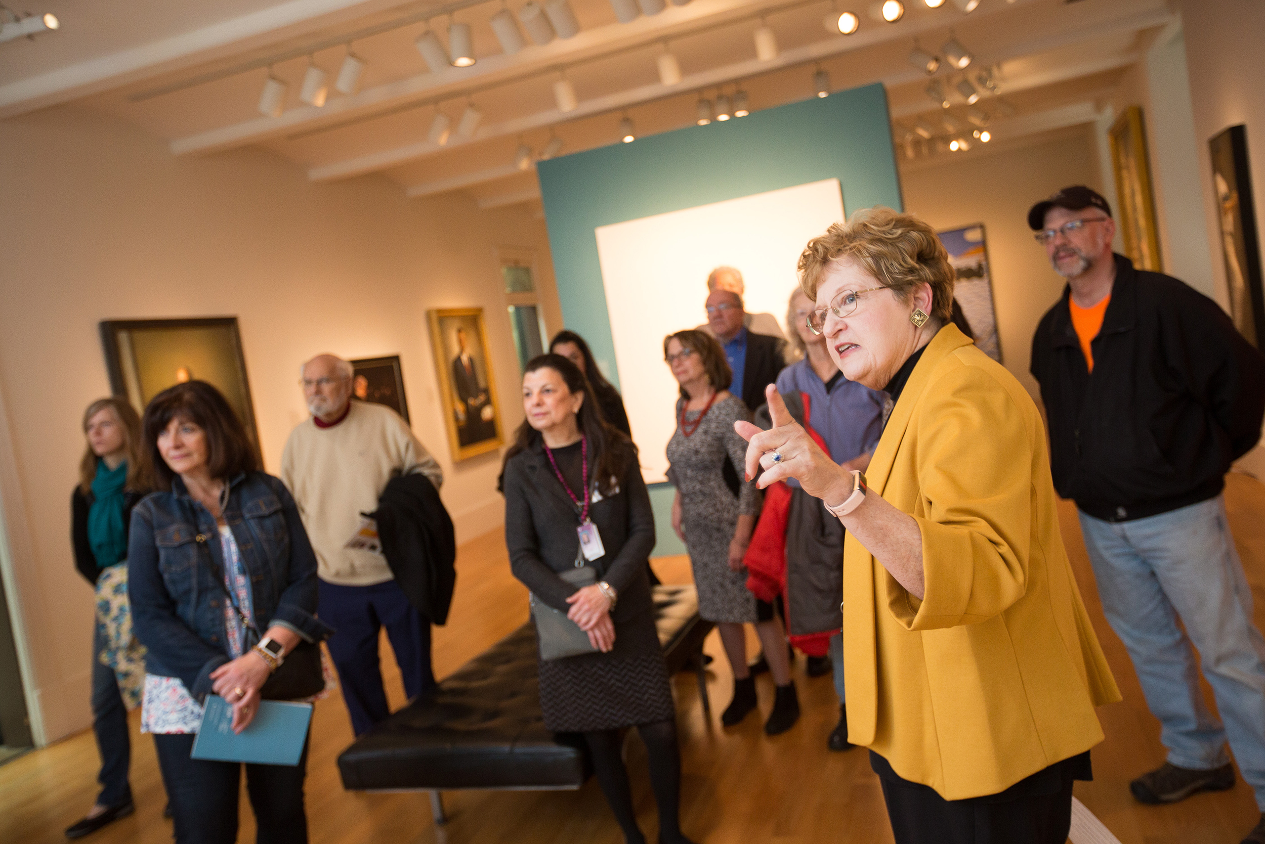 Docent in a yellow jacket giving a tour in the gallery